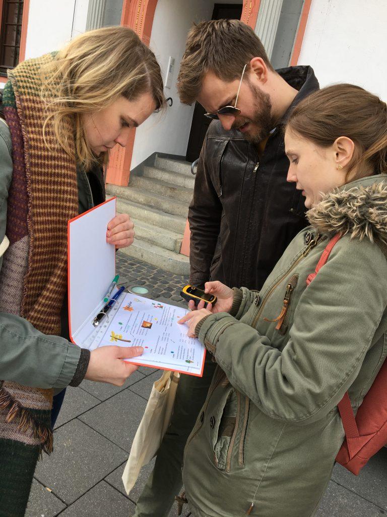 Drei konzentrierte Teilnehmer bei der Geocaching Tour in Mainz